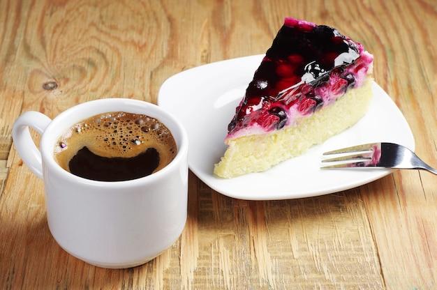 Kop warme koffie en cake met bessen op oude houten tafel