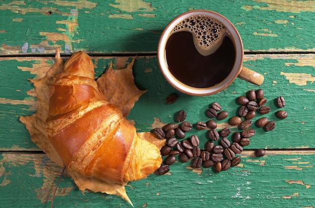Kop warme koffie en verse croissants op oude groene houten ondergrond, bovenaanzicht
