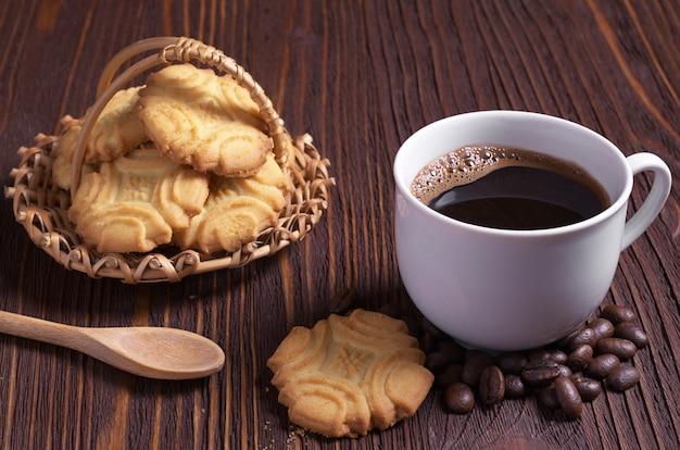 Kop warme koffie en zandkoekkoekjes op bruin houten tafel