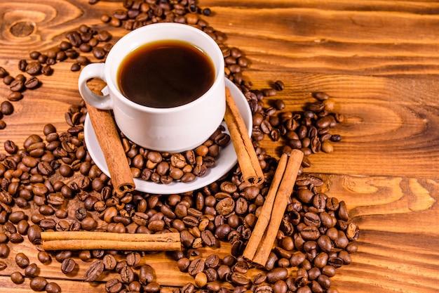 Kop warme koffie, kaneelstokjes en verspreide koffiebonen op rustieke houten tafel