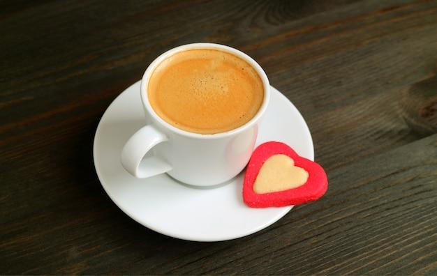 Kop warme koffie met een hartvormige boterkoekje op donkere bruine houten tafel