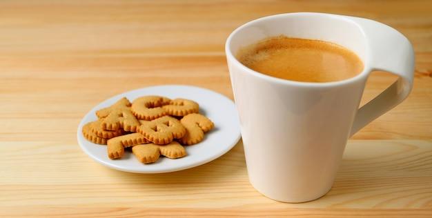 Kop warme koffie met een plaat van koekjes op houten tafel
