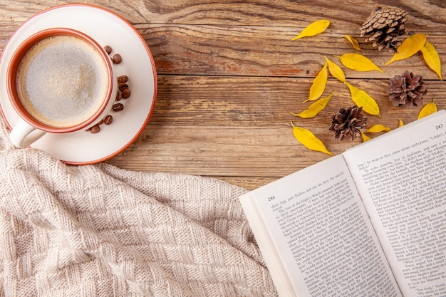 Kop warme koffie met geopend boek op houten achtergrond. herfst concept