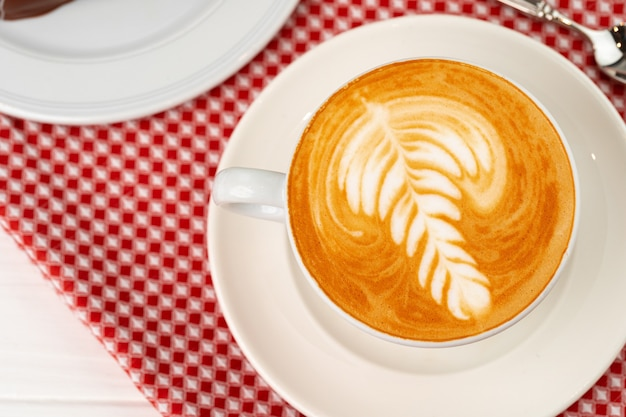 Kop warme koffie met kunst op schuim close-up