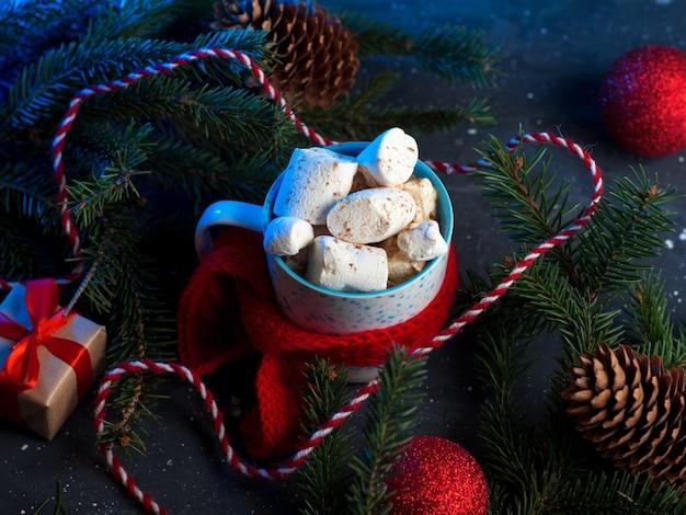 Kop warme koffie of chocolademelk met marshmallows, rode gebreide sjaal, kerstdecor, ballonnen en cadeaus