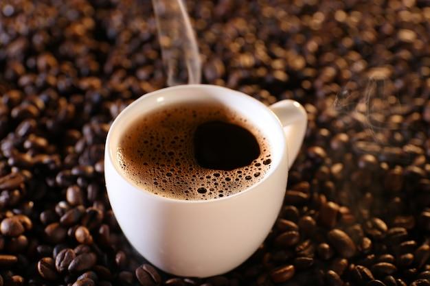 Kop warme koffie op koffiebonen