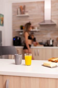Kop warme koffie op tafel tijdens het ontbijt in de thuiskeuken met een zorgeloze vrouw in zwarte lingerie. jonge sexy verleidelijke blode dame met tatoeages.