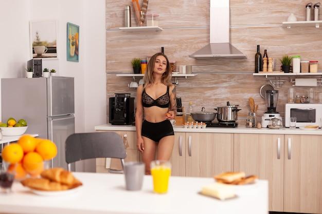 Kop warme koffie op tafel tijdens het ontbijt in de thuiskeuken met zorgeloze vrouw in zwarte lingerie