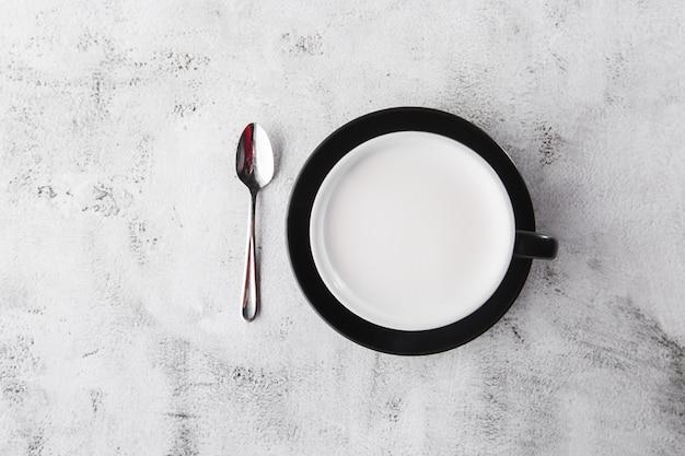 Kop warme melk in donkere kop geïsoleerd op lichte marmeren achtergrond. bovenaanzicht, kopieer ruimte. reclame voor café-menu. coffeeshop menu. horizontale foto. traditionele drankjes voor de winter