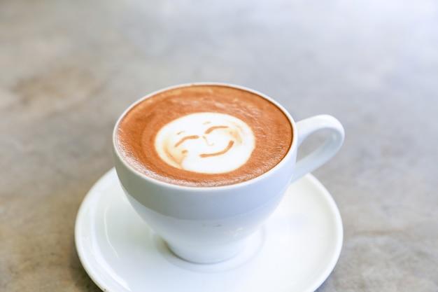 Kop warme smakelijke cappuccino met een glimlach als kunst latte op een positieve ochtendkoffie