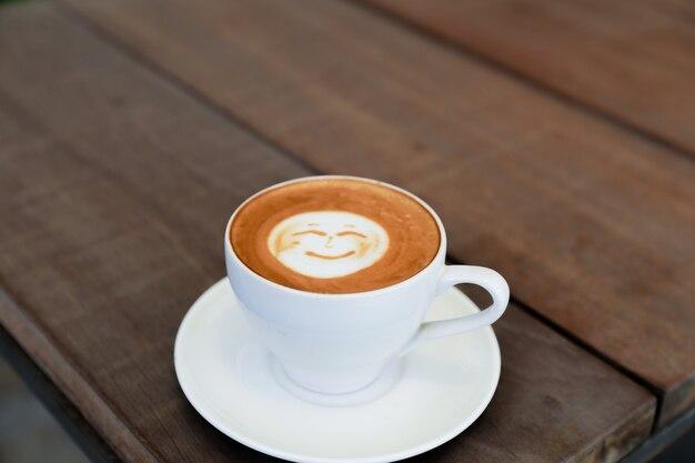 Kop warme smakelijke cappucino met glimlach als kunst latte. één positieve ochtendkoffie voor de dag. bovenaanzicht. witte kop met plaat op houten tafel achtergrond.