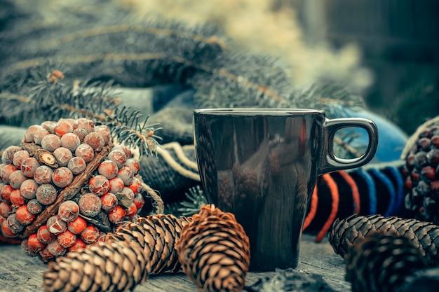 Kop warme thee op een rustieke houten tafel. stilleven van kegels, touw, patskthread, dennentakken.