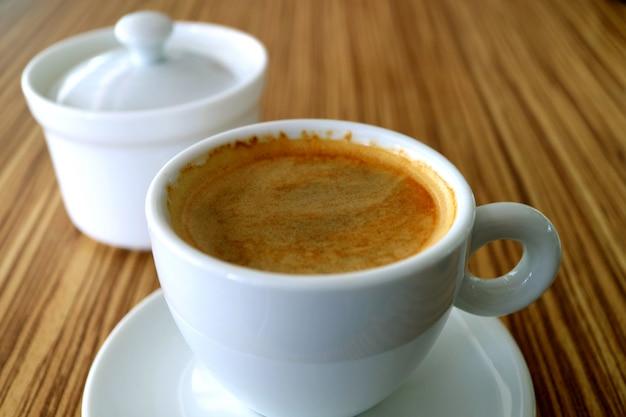 Kop warme zwarte koffie met een suikerpot geserveerd op een tafel