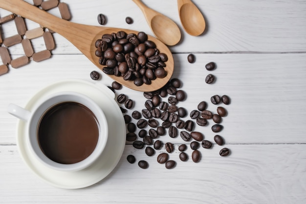 Kop zwarte koffie en koffiebonen goede essentials op witte houten lijst. bovenaanzicht.