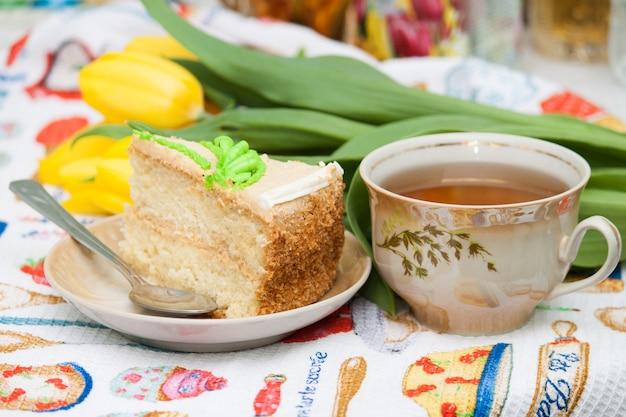 Kop zwarte thee, gele tulpen, smakelijke koekjescake, ontbijt voor mooie vrouw, vriendin, moeder.