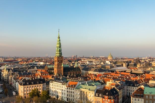 Kopenhagen, denemarken - oktober 2018: skyline in avondlicht. de oude binnenstad van kopenhagen en koperen spiel van nikolaj contemporary art center.
