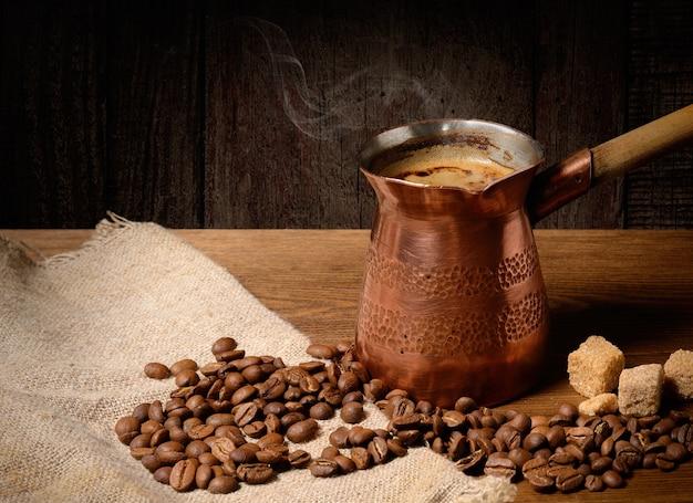 Koper cezve (turka) met warme vers gezette koffie op houten achtergrond met koffiebonen