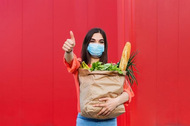 Koper draagt een beschermend masker. winkelen tijdens de covid 19, coronavirus pandemische quarantaine. vrouw in medische masker houdt een papieren zak met voedsel, fruit en groenten