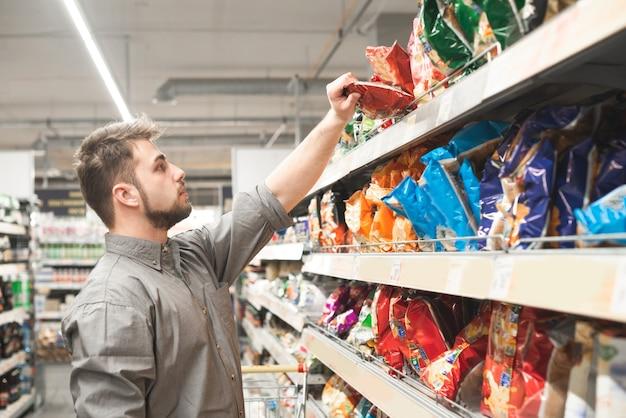 Koper draagt een overhemd en koopt een snack bij een supermarkt.