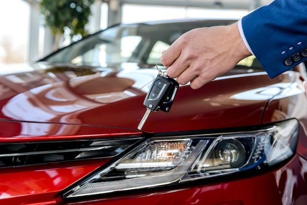 Koper houdt sleutels van auto, op achtergrond van rode auto