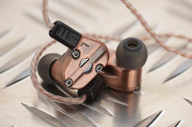 Koper metallic hybride dynamische driver gebalanceerde armatuur oordopjes op de aluminium metalen plaat.