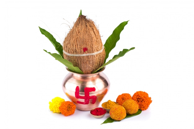 Koperen kalash met kokos, mangoblad, haldi, kumkum en snoepjes met goudsbloembloemdecoratie op een witte achtergrond. essentieel in hindoe-puja.