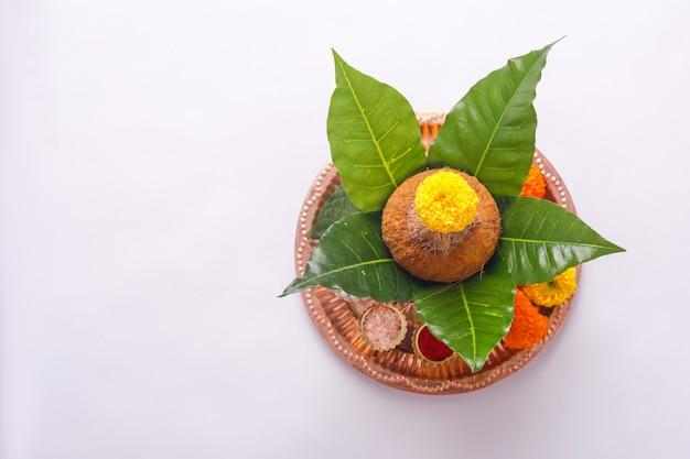 Koperen kalash met kokosnoot, blad en bloemendecoratie. essentieel in hindoe puja.