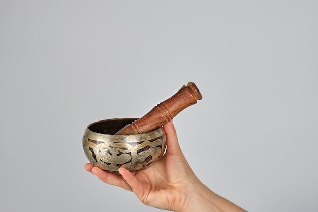 Koperen klankschaal en houten stok in vrouwelijke hand