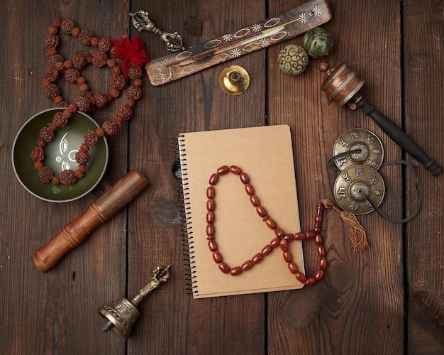 Koperen klankschaal, gebedskralen, gebedstrommel en andere tibetaanse religieuze voorwerpen voor meditatie