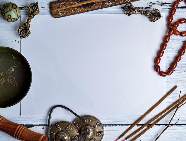 Koperen klankschaal, gebedskralen, gebedtrommel, stenen ballen en andere tibetaanse religieuze voorwerpen voor meditatie