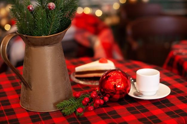 Koperen kruik kerstspar takken en kopje koffie staat op tafel straat café