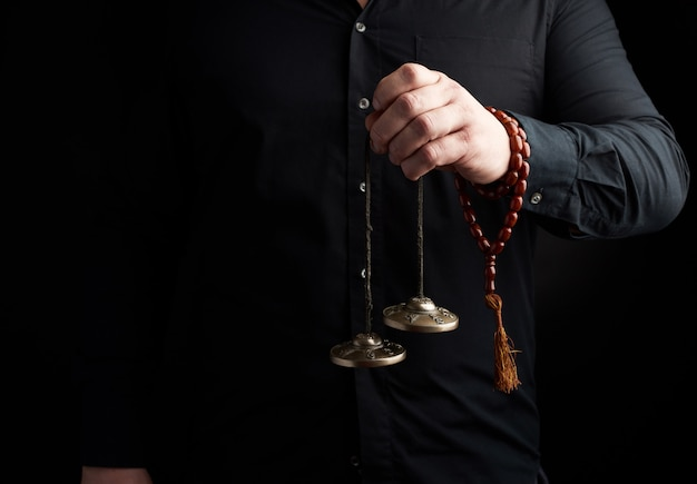Koperen tibetaanse kartaly houdt de hand van de man in het donker