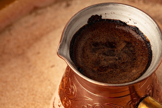 Koperen turk met koffie brouwen in zand close-up.