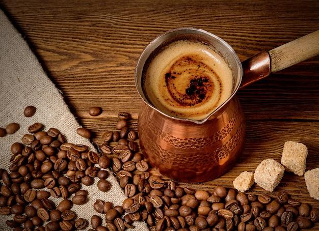 Koperen turk met vers gezette koffie op houten achtergrond met koffiebonen