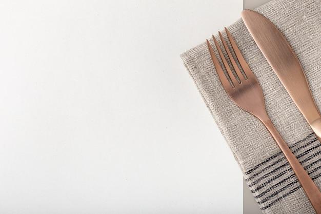 Koperen vork en mes op gerecycled papier