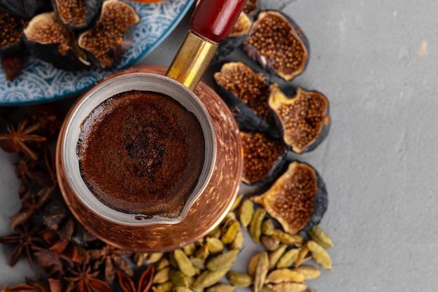 Koperkoffie turk met gedroogde zaden en vruchten op grijze oppervlakte