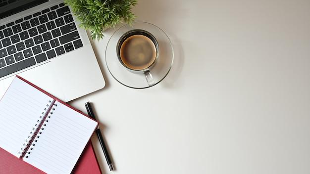 Kopieer de ruimte bureau met laptop, laptop en pen met koffie. bovenaanzicht tafel.