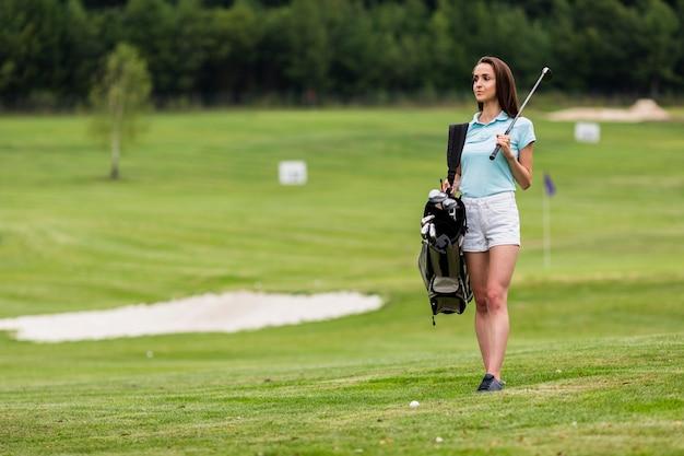 Kopieer de ruimte jonge golfspeler golfclubs houden