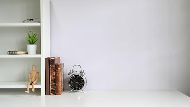 Kopieer de ruimte met boeken, alarm op witte tafel.
