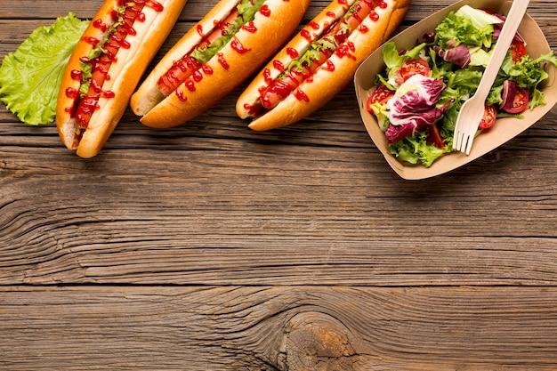 Kopieer de ruimte met salade en hotdogs