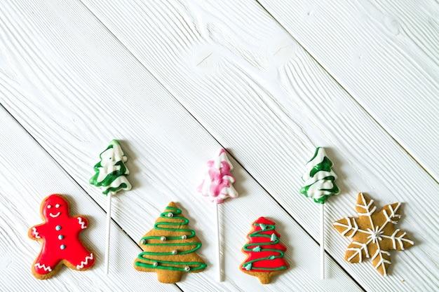 Kopieer de ruimte met traditionele kerstsnoepjes op witte houten achtergrond. riet van het suikergoed, ronde sneeuwvlok en gemberman, sterlolly. bovenaanzicht plat leggen. kerst concept