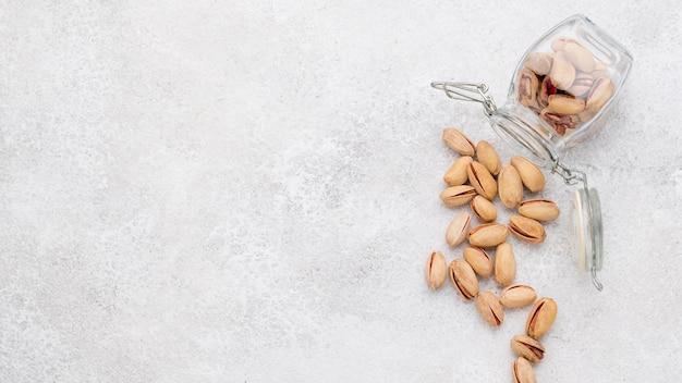 Kopieer de ruimte omgevallen pot gevuld met pistachenoten op marmeren tafel