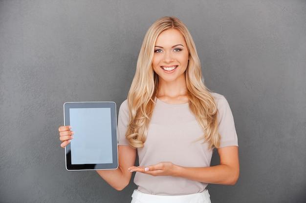 Kopieer de ruimte op haar tablet. vrolijke jonge vrouw die digitale tablet vasthoudt en ernaar wijst