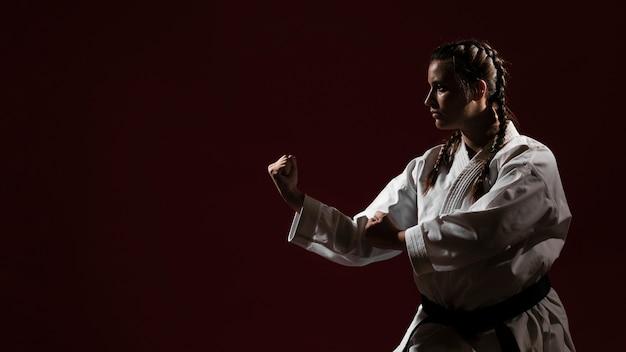 Kopieer de ruimte rode achtergrond en vrouw in witte karate uniform
