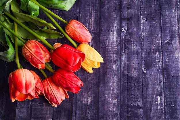 Kopieer ruimte boeket van oranje en gele tulpen over een rustieke houten tafel