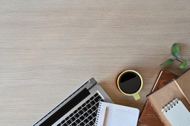 Kopieer ruimte bureau met laptop, boeken en potlood met koffie op werkruimte houten tafel.