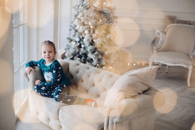 Kopieer ruimte foto van een smiley klein meisje, zittend op een zachte gezellige bank met kerstboom. vakantie concept