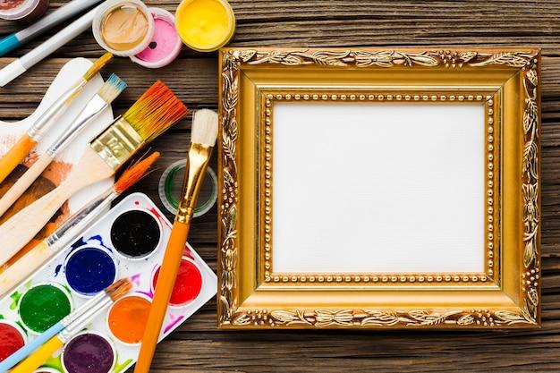 Kopieer ruimte gouden canvas frame en borstels