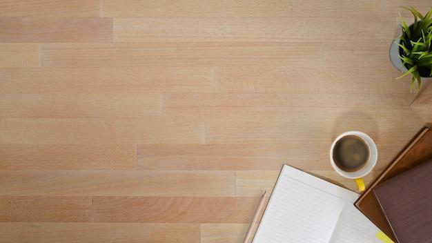 Kopieer ruimte houten tafelblad weergave met notebookpapier, koffie en potlood.