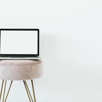 Kopieer ruimte mockup scherm laptop op stijlvolle kruk op wit